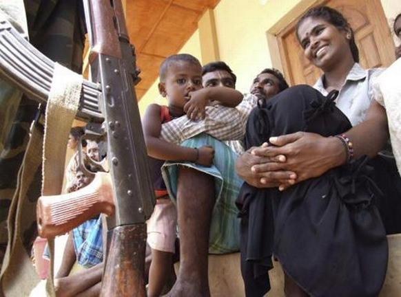 A soldier, left, stands near a Sri Lankan ethnic Tamil family before they were sent back to their village, at a transit camp for displaced civilians in Trincomalee, Sri Lanka, on September 23, 2009 AP