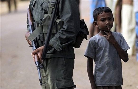 A young Sri Lankan refugee displaced during the final stages of the fighting, stands beside a soldier