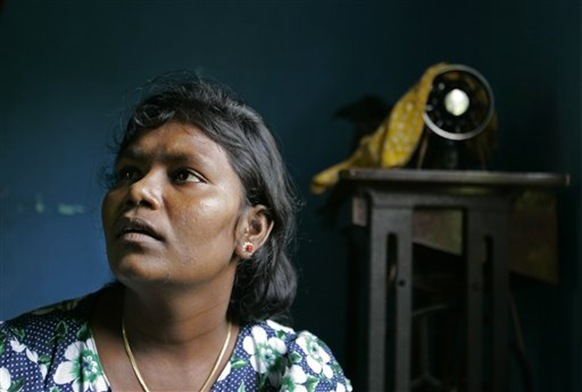 This Nov. 13, 2009 photo shows Vairamutto Bavani looking on with her sewing machine seen in the background of her house in Kalkudah, about 230 kilometers (143 miles) north east of Colombo, Sri Lanka. Three years ago, Bavani left her home in eastern Sri Lanka to attend her cousin's wedding in the north. Bavani lost six members of her family and both her legs to a bomb and spent months detained in an overcrowded refugee camp before finally returning home. Bavani is one of tens of thousands of refugees who are struggling to rebuild their lives in post-war Sri Lanka, often under tight control from the government. During the final months of the war, nearly 300,000 mostly Tamil civilians were trapped between rebels and advancing government troops, and these refugees are now in various stages of limbo. (AP Photo/Eranga Jayawardena)