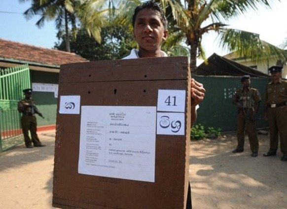 A Sri Lankan election worker carries ballot boxes in Colombo ahead of the island state's presidential election