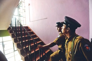 Policemen stand guard in the stairwell of the pro-opposition Lanka newspaper offices in Delkanda, a Colombo suburb, yesterday