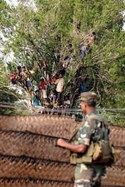 Sri Lankan military stand guard as war-displaced civilians look on at a state-run internment camp in Vavuniya in 2009