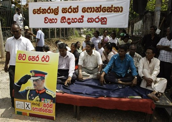 Supporters of defeated Sri Lankan presidential candidate Gen. Sarath Fonseka, seen left on a placard, participate in a sit-in protest demanding his immediate release, in Colombo - ap