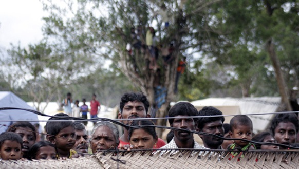 Displaced Sri Lankan Tamils gaze past a fence at an internment camp in Vavuniya in November 2009. (Reuters)