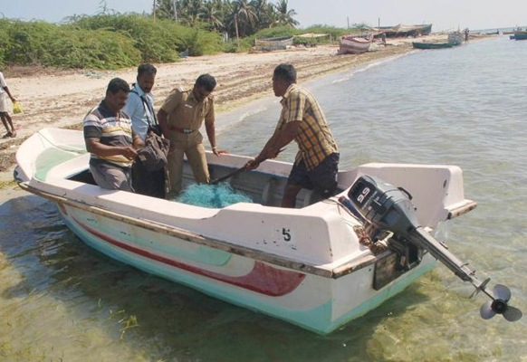 Security personnel inspecting the Sri Lankan boat, which was found abandoned in Rameswaram on Wednesday.Photo L. Balachandar Hindu