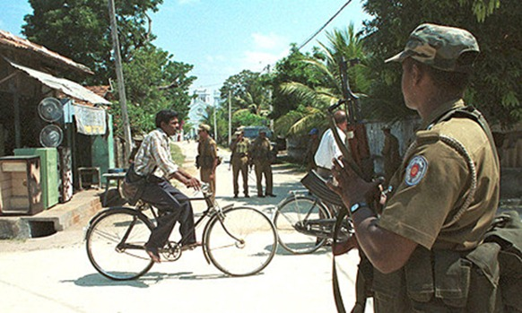 "FOR USE WITH ""SRI LANKA"" -- Sri Lankan police stand guard at a check point as residents travel on  bicycles in Jaffna, Sri Lanka Friday March 5, 1999. There are over 1,000 check points all over the town manned by troops and police, fearing Tamil rebel attacks. Civilian life is far from normal despite attempts by the government to restore civil administration since the town was captured  by government troops in1996 from Tamil rebels. (AP Photo Gemunu Amarasinghe)"