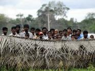 Displaced Sri Lankan civilians look out from behind barbed wire fences surrounding their internment camp in Vavuniya afp