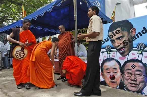 Sri Lankan Buddhist monks look on as they participate in a protest outside the United Nation's office in Colombo, Sri Lanka, Wednesday, July 7, 2010. Sri Lankan protesters threatened hunger strikes and nationwide demonstrations Wednesday if the United Nations refused to halt its investigation into possible abuses committed during the final bloody months of the civil war. (AP Photo Eranga Jayawardena)