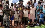 Sri Lankan war-displaced civilians look on at a state-run internment camp in Vavuniya in 2009