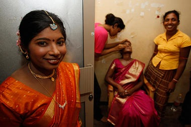 A former female Tamil Tiger rebel dressed in bridal attire looks on as others dress up another bride during a mass wedding ceremony at a government rehabilitation camp near Vavuniya in northern Sri Lanka in June.  Eranga Jayawardena AP