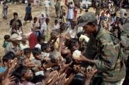 A Sri Lankan soldier hands out food to Tamils