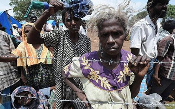 Internally displaced Sri Lankan people wait behind barbed wire at Menik Farm refugee camp in Cheddikulam  Photo: AFP GETTY