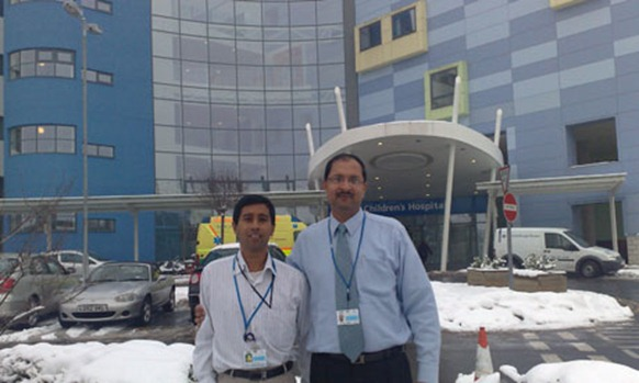 Sri Lankan doctor Anuruddha Padeniya, left, outside the John Radcliffe hospital, Oxford, where he worked during his UK placement. Photograph: GHWA