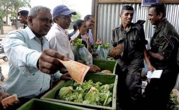 AFP – Sri Lankan soldiers sell vegetables in Colombo on January 7. Sri Lanka's army opened a chain of food …