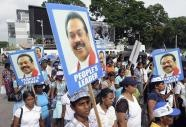 Sri Lankan government supporters carry portraits of President Mahinda Rajapakse