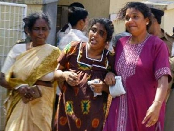 Relatives react after identifying the bodies of slain workers from the international aid agency Action Contre La Faim (ACF), at a hospital entrance in Trincomalee, August 8, 2006. (REUTERS)