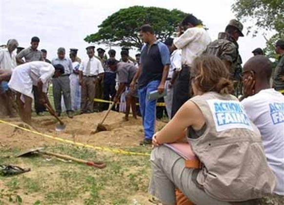 Representatives of international relief agency Action Against Hunger, right, look on as workers exhume the remains of one of 17 aid workers. (Photo:AP)