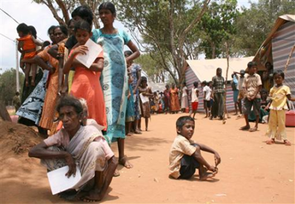 Tamil civilians stand next to their huts in a refugee camp located on the outskirts of the town of Vavuniya in northern Sri Lanka May 6, 2009. REUTERS-Stringer