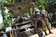Sri Lankan soldiers stand guard next to a tank which was captured by the army from the LTTE (AFP File, Pedro Ugarte)