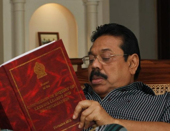 AP In this file photo, Sri Lankan President Mahinda Rajapaksa goes through the Lessons Learnt and Reconciliation Commission report, that investigated alleged wartime abuses during the country's civil war, in Colombo.
