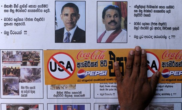 AHRC Photo: A Buddhist monk holds a sticker calling for the boycott of U.S products in Colombo March 23, 2012.)