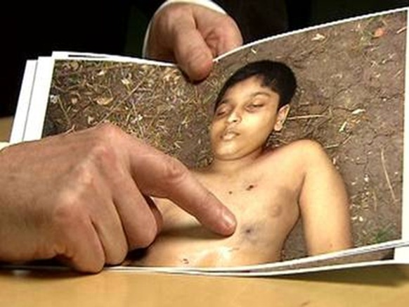 Derrick Pounder points out one of the five bulletwounds in the body of Balachandran Prabhakaran, 12, in Channel 4's Killing Fields Channel 4