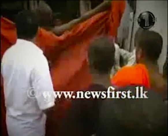 A Buddhist monk flashes a mosque in Dambulla. Screen grab from News 1st TV footage.