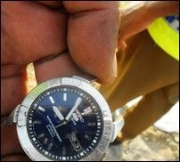 An SL police officer holding the wristwatch of the slain victim