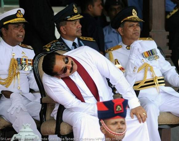 Sri Lankan President Mahinda Rajapaksa bends to catch a glimpse of sky divers in Colombo. Ishara S.Kodikara / AFP/Getty Images