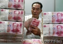 A Chinese bank staff member counts stacks of 100-yuan n in Huaibei, east China's Anhui province on August 17, 2012 (AFP/File)