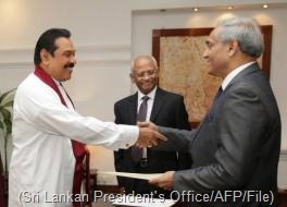 President Mahinda Rajapakse (left) shakes hands with Mohan Peiris after appointing him chief justice on January 15 (Sri Lankan President's Office/AFP/File)