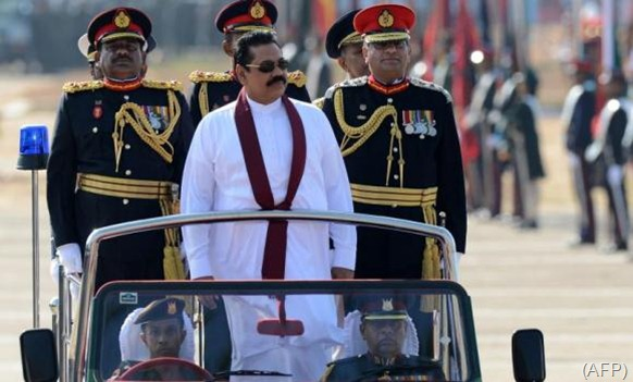 Sri Lanka President Mahinda Rajapaksa looks on as he rides in a vehicle during a Victory Day parade in southern town of Matara. (AFP)